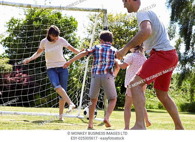 Family Playing Football In Garden Together