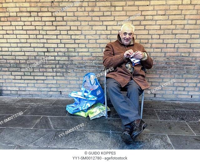 Tilburg, Netherlands. Lonely man, selling his 'Homeless Magazine' from his plastic bags, while sitting in a foldable chair against a wall