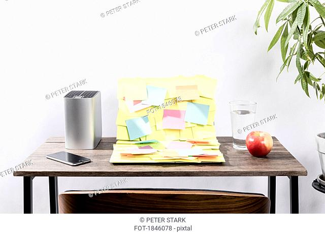 Adhesive notes covering laptop on desk in office