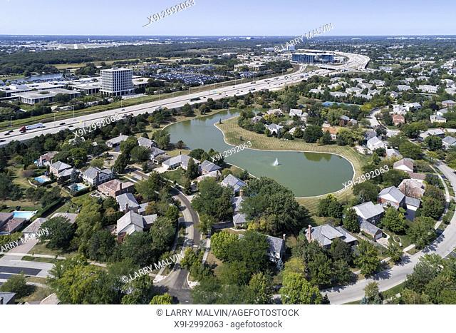 Aerial view of a neighborhood with pond beside a major highway in the suburb of Glenview, IL. USA