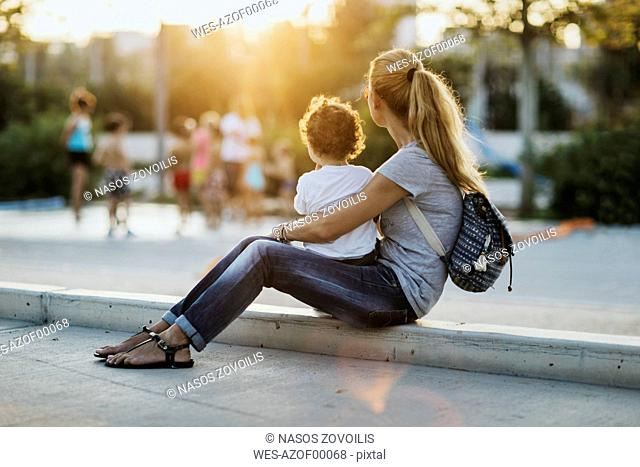 Mther sitting with her little son on a square at sunset