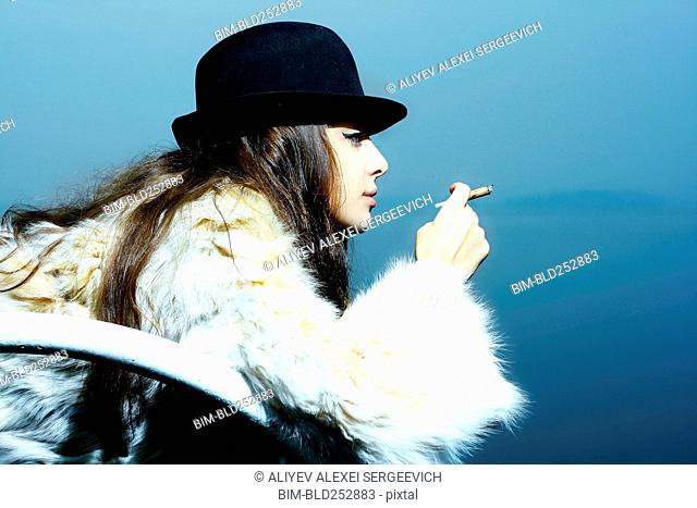 Portrait of glamorous woman wearing fur coat smoking cigarette