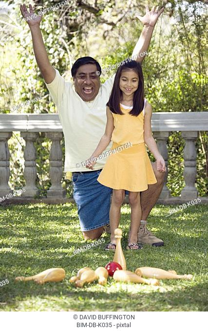 Indian father and daughter playing lawn bowling