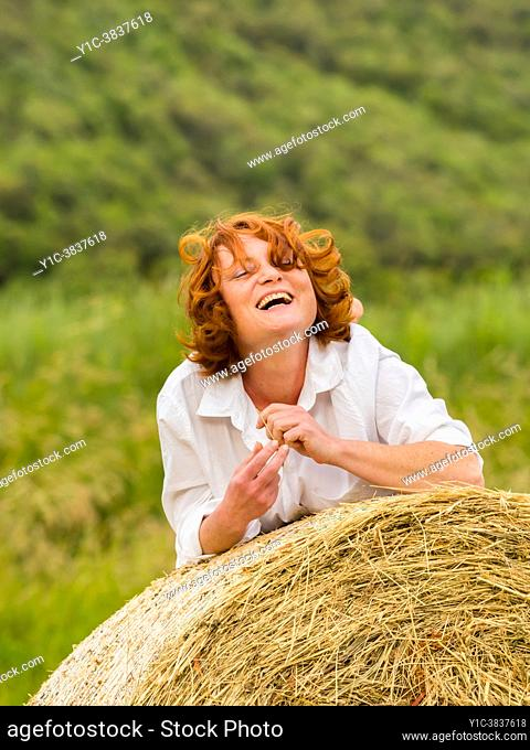 Mature woman on countryside haystack is laughing squinting eyes