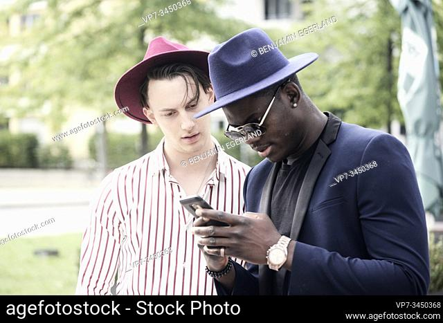 Two men looking at phone. Munich, Germany