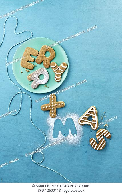 Letter biscuits spelling 'Merry Xmas' with icing sugar