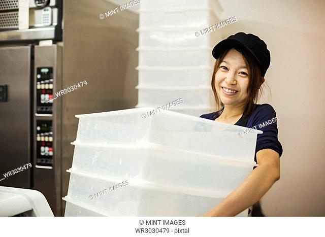 Woman working in a bakery, wearing baseball cap, carrying stack of white plastic crates