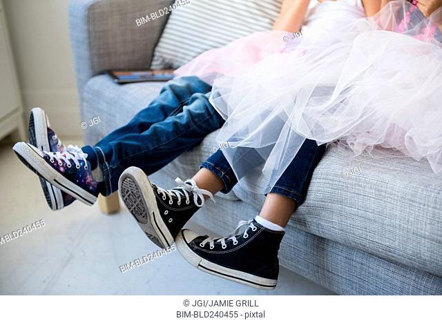 Legs of girls wearing tutus on sofa