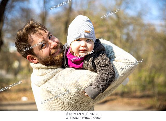 Portrait of happy father carrying daughter in park