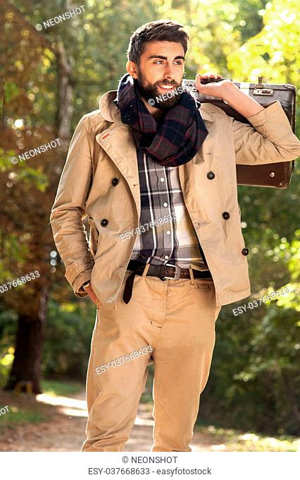 Fashion photo of young handsome man with suitcases in park. Autumn. Men wearing coat and scarf. Sunny day
