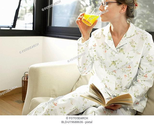 Young woman in pajama drinking orange juice