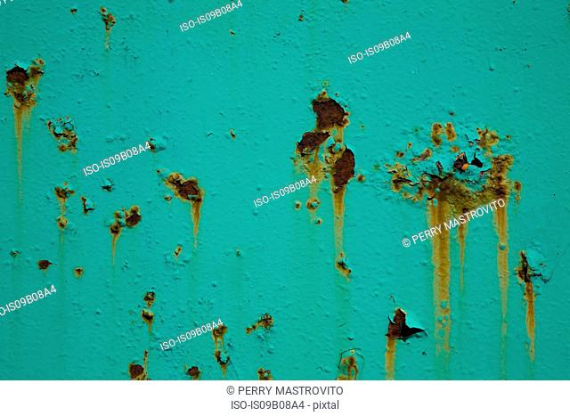 Peeling turquoise paint and rust on metal surface