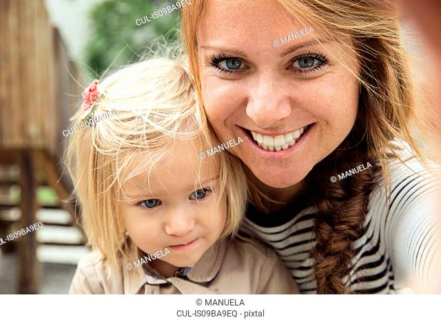Portrait of mother and toddler daughter in park, close up