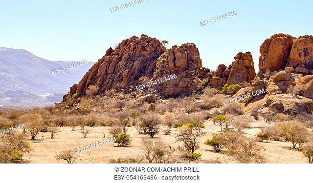 sunny illuminated landscape including a rock formation seen in Namibia, Africa