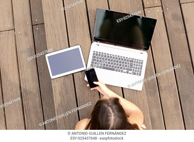 Woman using multiple devices phone laptop and tablet lying in a wood bench in a park