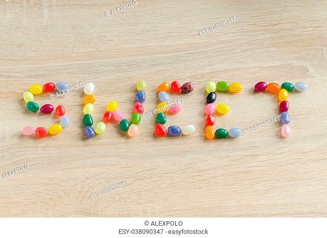 Word sweet from jelly beans on wooden background