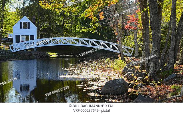 Somesville Maine beautiful curved bridge over water pond and white house in fall foliage colors in October in New England