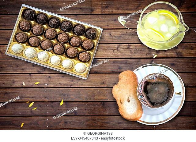 On the surface of the wooden table coffee Cup with croutons, chocolates, lemon with ice