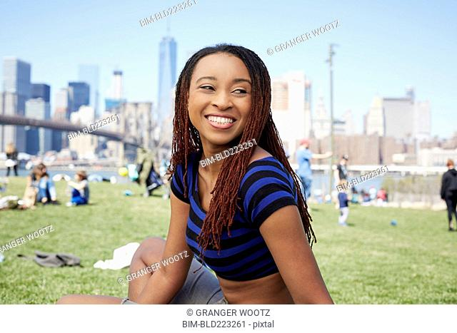 Smiling Black woman sitting in grass at waterfront