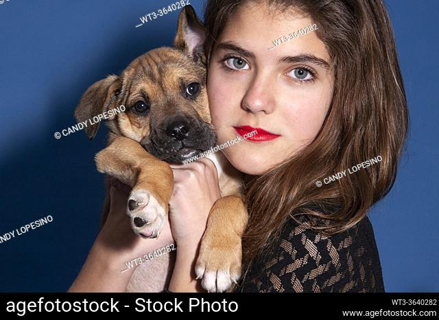 Young girl and her dog puppy at home looking at the camera