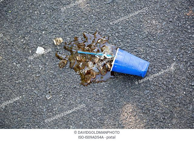 Spilled soft drink with plastic cup and ice cubes on tarmac