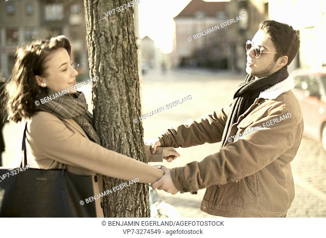 young teenage couple holding hands around tree, in city Cottbus, Brandenburg, Germany