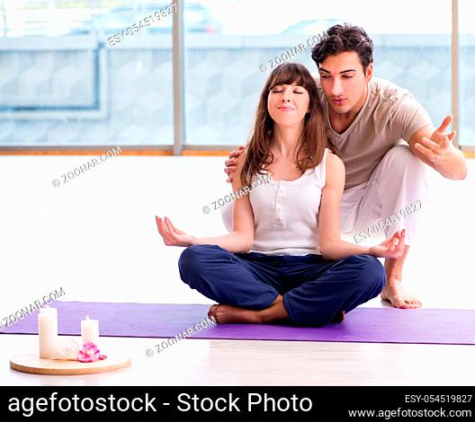 The personal coach helping during yoga session