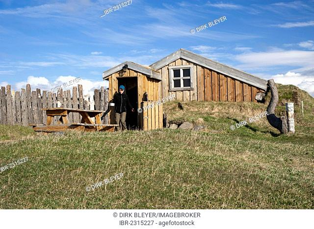 Woman walking through a door carrying a pot, wooden cabin, campground, Moeðrudalur farm, Iceland's highest situated farm, Highlands of Iceland, Iceland, Europe