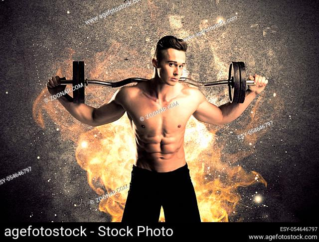 A strong athletic guy looking seductive while working out with weight in front of a burning fire concrete wall and big flames concept