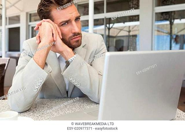 Frowning businessman looking at his laptop at table having coffee
