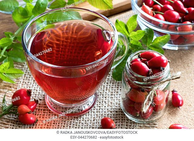 A cup of rose hip tea on a table, with fresh rosehips in the background