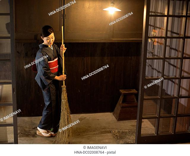 Mid Adult Japanese woman in kimono sweeping with broom at entrance