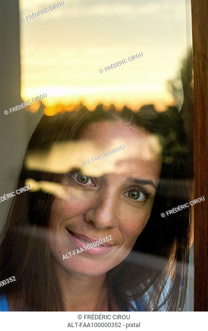 Woman looking through window at camera, portrait