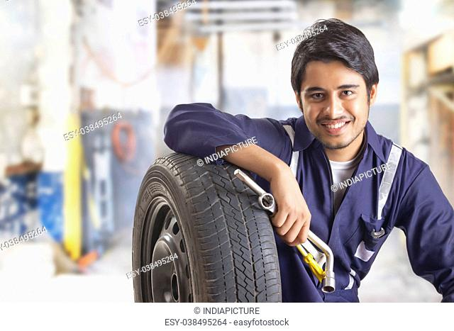 Portrait of car mechanic with spare tyre and hand tools in garage