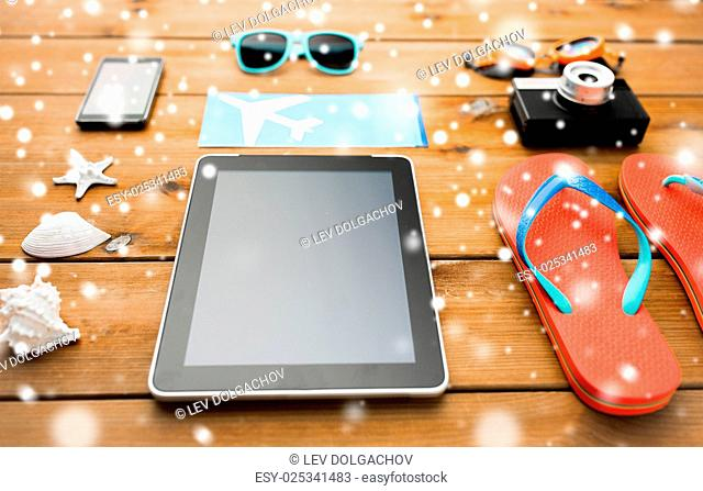 travel, tourism, technology and winter holidays concept - tablet pc computer, airplane ticket and beach stuff over snow