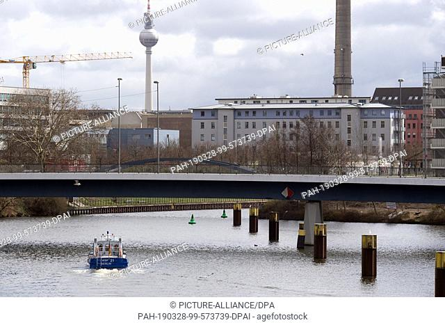 25 March 2019, Berlin: A boat of the water police drives in front of the scenery of the television tower from the north port coming over the Hohenzollernkanal...