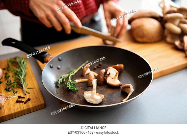 Fresh sliced mushrooms are sitting in a pan on a wooden board, ready to be put on the stove. In the background, a woman slices more fresh mushrooms