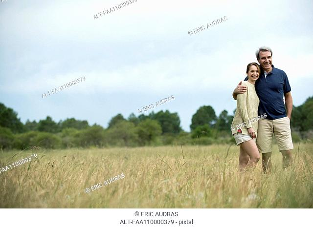 Couple standing together in tall grass