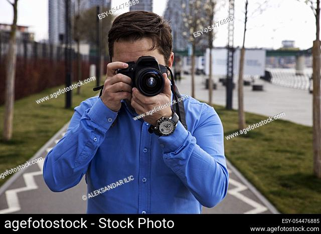Photographer photographing outdoors. Shooting in urban city environment
