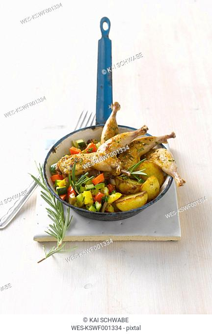 Quail legs with potato wedges on ratatouille