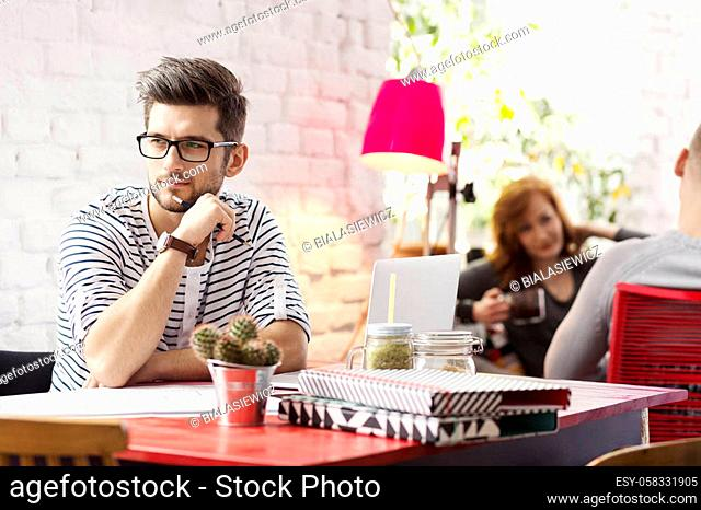 Freelancer working with computer in industrial office with brick wall