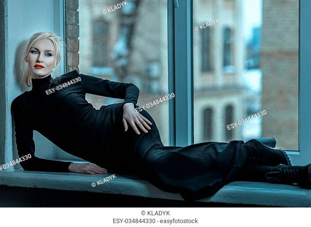 Beautiful and cold woman lies on a windowsill with sadness in his eyes