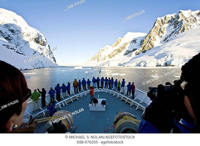 The Lindblad Expedition ship National Geographic Explorer transits Lemaire Channel in late evening light on the west side of the Antarctic peninsula in...