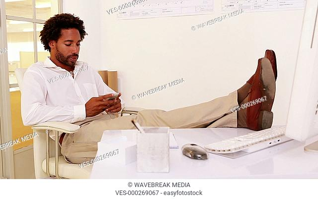 Businessman sitting with feet up talking on phone