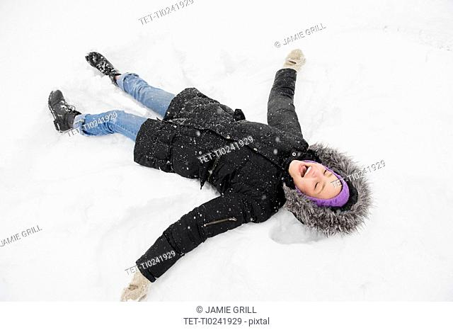 Young woman making snow angel