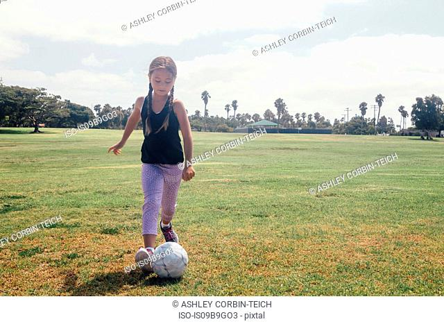 Schoolgirl kicking soccer ball on school sports field
