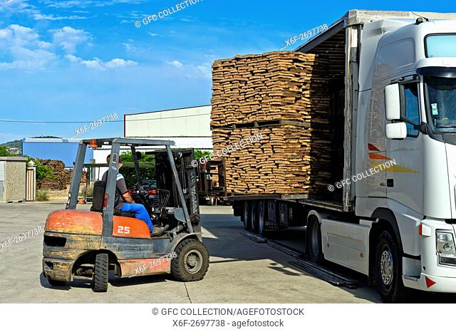 A forklift uploads pallets of graded cork on a truck, cork factory Novacortiça, São Brás de Alportel, Algarve, Portugal