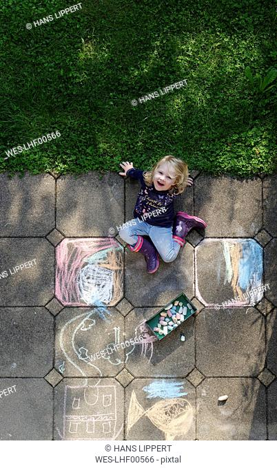 Smiling little girl drawing with chalk outdoors, top view
