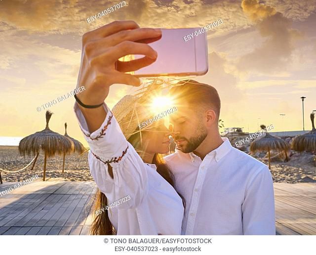 Couple young selfie photo in beach together vacation sunrise at Spain