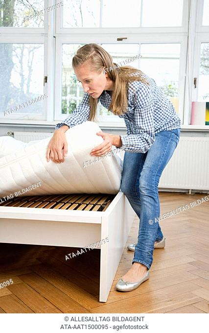 Woman raising mattress